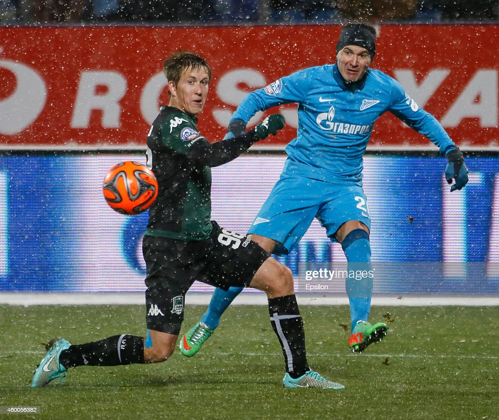 Viktor Fayzulin of FC Zenit St. Petersburg (R) passes the ball as Sergei Petrov of FC Krasnodar defends during the Russian Football League Championship match between FC Zenit St. Petersburg and FC Krasnodar at the Petrovsky stadium on December 6, 2014 in St. Petersburg, Russia.