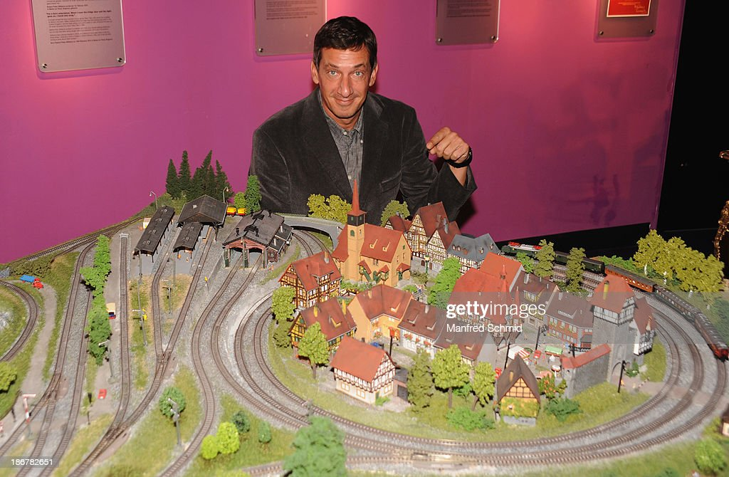 Viktor Gernot poses next to a toy train of Peter Alexander during a press event for the Peter Alexander charity auction at Madame Tussauds on October 29, 2013 in Vienna, Austria.
