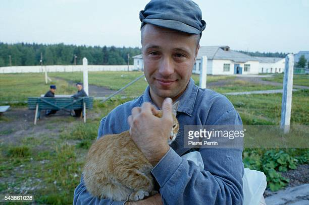 Viktor Makarov a prisoner of Perm 35 holds a cat while taking a walk in the yard | Location The Urals USSR