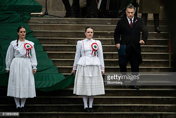 Viktor Orban Hungary's prime minister right arrives for an official address outside the National Museum of Hungary in Budapest Hungary on Tuesday...