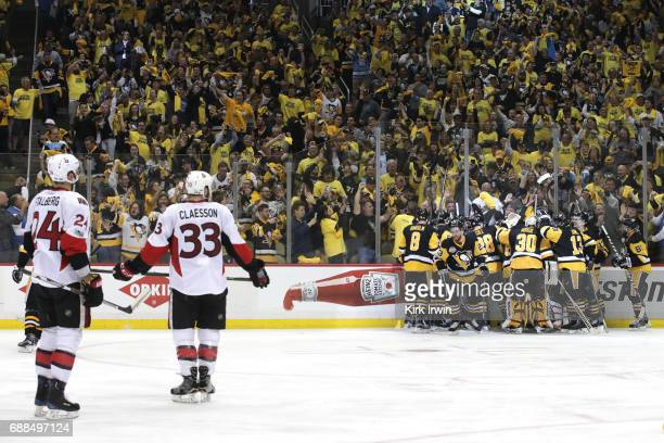 Viktor Stalberg and Fredrik Claesson of the Ottawa Senators look on as the Pittsburgh Penguins celebrate after Chris Kunitz scored the game winning...