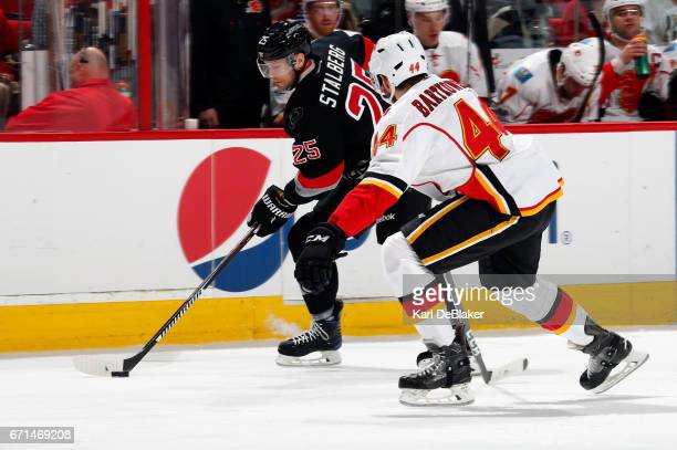 Viktor Stalberg of the Carolina Hurricanes controls the puck along the boards away from Matt Bartkowski of the Calgary Flames during an NHL game on...