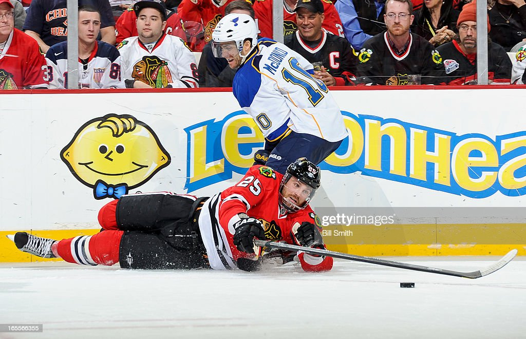 Viktor Stalberg #25 of the Chicago Blackhawks reaches toward the puck as Andy McDonald #10 of the St. Louis Blues skates next to the boards during the NHL game on April 04, 2013 at the United Center in Chicago, Illinois.