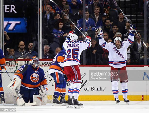 Viktor Stalberg of the New York Rangers scores at 1837 of the second period against Jaroslav Halak of the New York Islanders and is joined by Dominic...