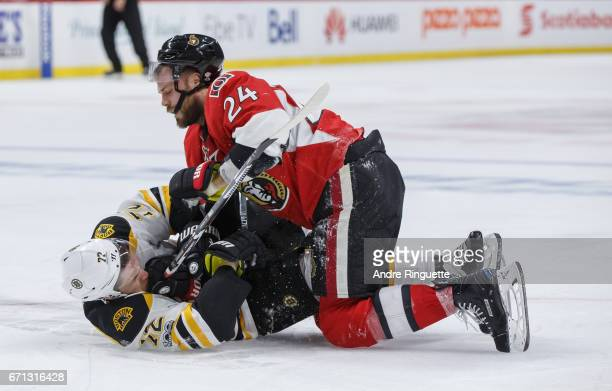 Viktor Stalberg of the Ottawa Senators pins Frank Vatrano of the Boston Bruins to the ice as the two get tangled up behind the play in Game Five of...