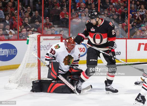 Viktor Stalberg of the Ottawa Senators watches the loose puck as Scott Darling of the Chicago Blackhawks makes a save in the second period at...