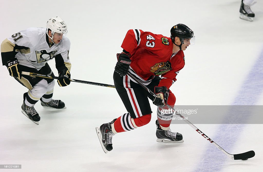 Viktor Svedberg #43 of the Chicago Blackhawks moves up the ice under pressure from Derrick Pouliot #51 of the Pittsburgh Penguins during an exhibition game at United Center on September 19, 2013 in Chicago, Illinois. The Penguins defeated the Blackhawks 4-3 in a shootout.