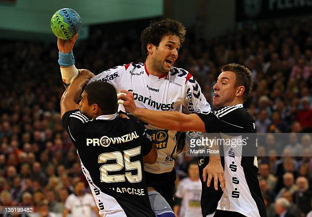 Viktor Szilagyi of FlensburgHandewitt is challenged by Daniel Narcisse and Filip Jicha of Kiel during the Toyota HBL match between SG...