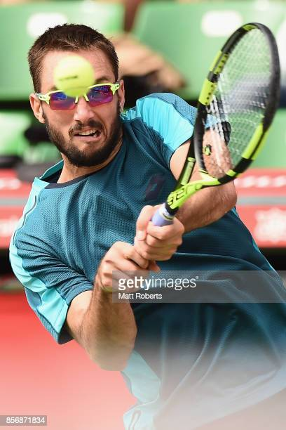 Viktor Troicki of Serbia plays a backhand against Milos Raonic of Canada during day two of the Rakuten Open at Ariake Coliseum on October 3 2017 in...
