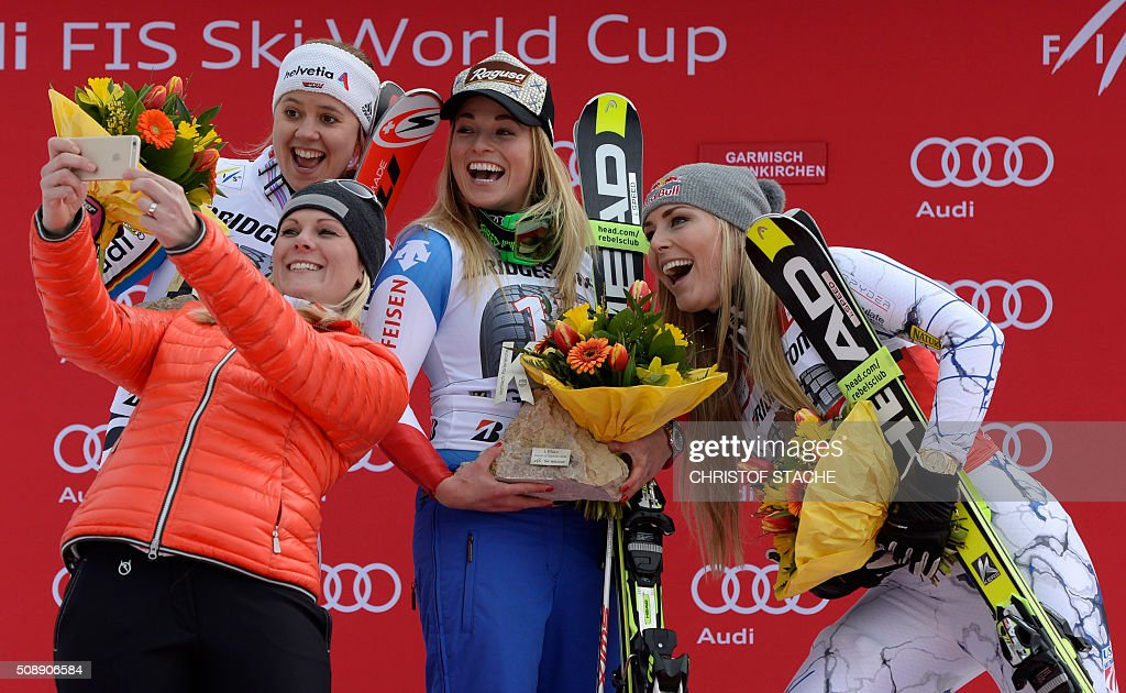 Viktoria Rebensburg from Germany, former Austrian skier Nicole Hosp, Lara Gut from Switzerland and Lindsey Vonn from USA take a photo during the winner ceremony of the Ladies Super G competition race at the FIS Alpine Skiing World Cup in Garmisch-Partenkirchen, southern Germany, on February 7, 2016. Lara Gut from Switzerland won the competition, Viktoria Rebensburg from Germany placed second and Lindsey Vonn from USA placed third. / AFP / Christof STACHE