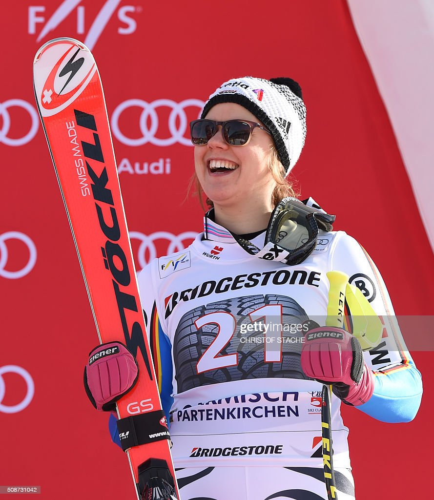 Viktoria Rebensburg from Germany laughs during the winner ceremony after the ladies downhill competition race at the FIS Alpine Skiing World Cup in Garmisch-Partenkirchen, southern Germany, on February 6, 2016. Lindsey Vonn from USA won the competition, Fabienne Suter from Switzerland placed second and Viktoria Rebensburg from Germany placed third. / AFP / Christof STACHE
