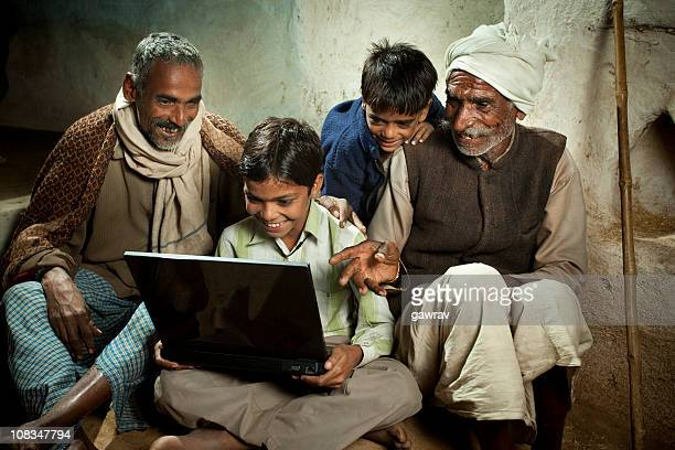 Village boy with father, grandfather and brother using a laptop