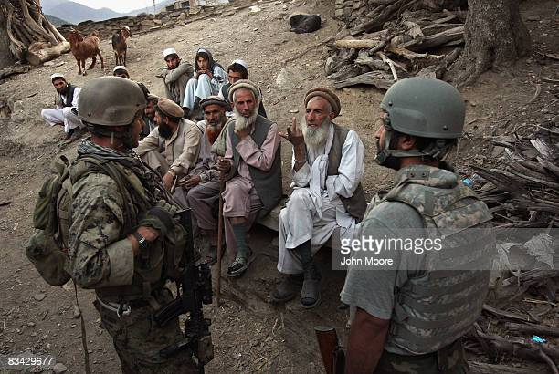 Village elders speak with a US Marine through an interpreter as American and Afghan forces search for weapons October 25 2008 in the Korengal Valley...