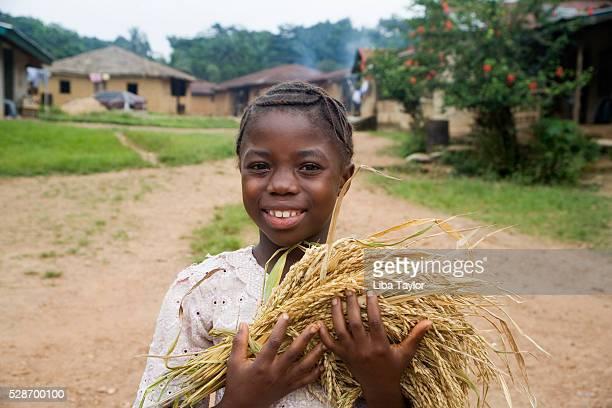 Village Girl Holding Wheat in Sierra Leone