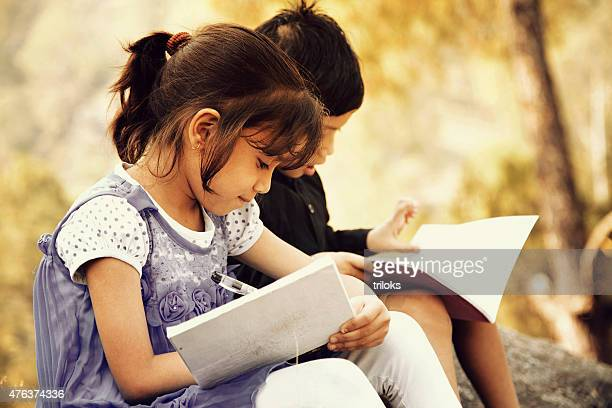 Village girl studying with her brother