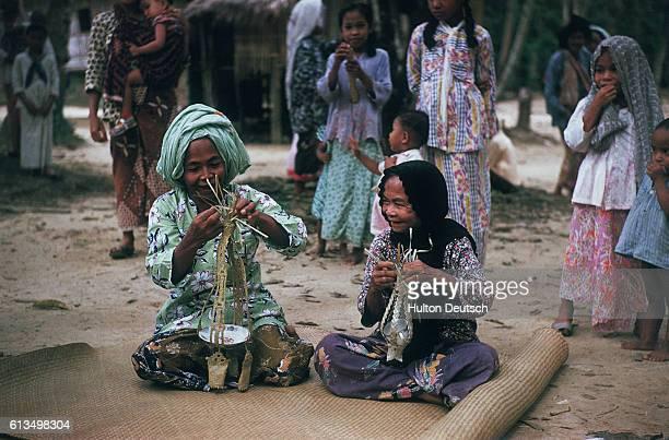 Village in Malaya women making macrame hanging baskets