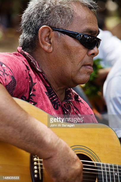 Village man performing on guitar, celebrating the arrival of government dignatories.
