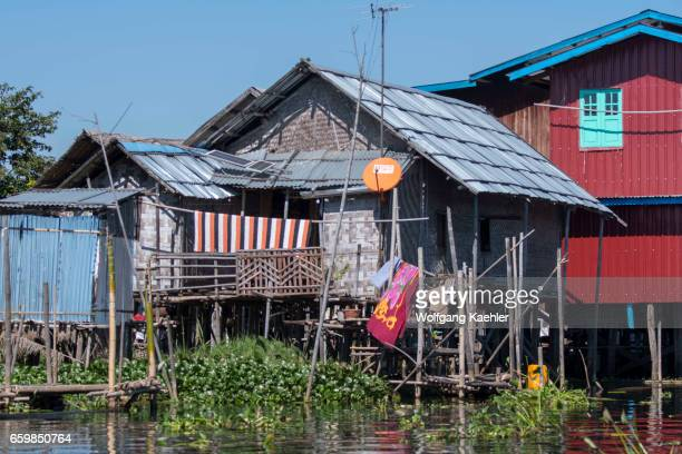A village scene with a house on stilts and a satellite dish in a village on stilts in Inle Lake in Myanmar