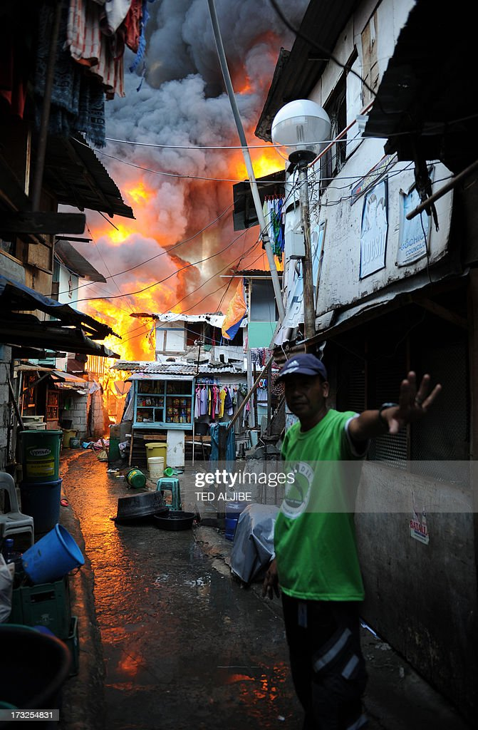 A village watchman signals to residents to stop going near their burning houses as fire engulfs a shanty town at the financial district of Manila on July 11, 2013, leaving more than 1,000 people homeless according to city officials. There were no immediate reports of casualties from the blaze, which occurred mid-morning amid government plans to relocate thousands of families living in areas vulnerable to floods and typhoons.
