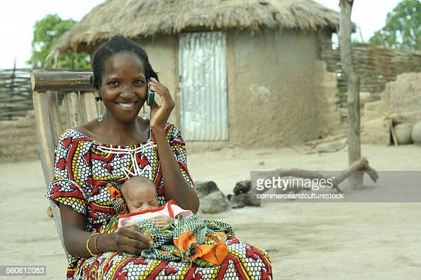 A village woman with a baby having a call