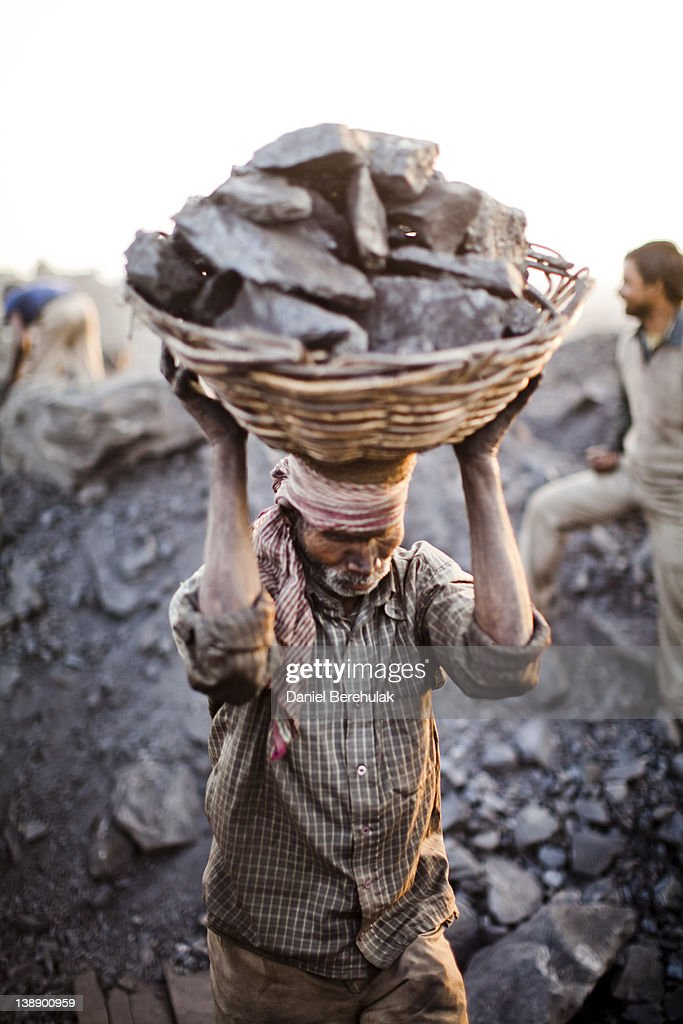 A villager carries a basket of coal scavenged illegally from an open-cast mine in the village of Jina Gora on February 11, 2012 near Jharia, India. Villagers in India's Eastern State of Jharkhand scavenge coal illegally from open-cast coal mines to earn a few dollars a day. Claiming that decades old underground burning coal seams threatened the homes of villagers, the government has recently relocated over 2300 families to towns like Belgaria. Villagers claim they were promised schools, hospitals and free utilities for two years, which they have not received. As the world's power needs have increased, so has the total global production of coal, nearly doubling over the last 20 years according to the World Coal Association.