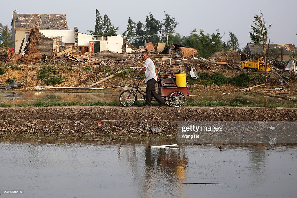 A villager carry away the property of the damaged house in Beichen Village of Chenliang Township in Funing, Yancheng, east China's Jiangsu Province on June 25, 2016. A total of 98 people were killed after severe storms in several towns in Jiangsu on Thursday, local rescue headquarters said on Friday. About 846 people sustained injuries, 200 of whom were seriously wounded, it said. More than 8,600 houses, two elementary schools and eight factory buildings were damaged in the counties of Funing and Sheyang, and parts of Yancheng City along the eastern coast of China on June 25, 2016 in Yancheng, China.