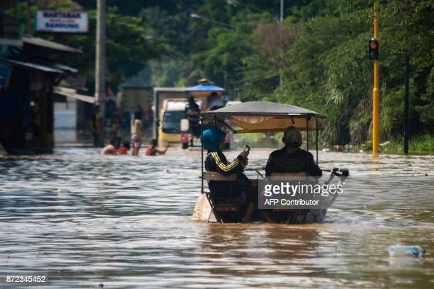A villager checks her mobile phone as she rides in a horsecart through a flooded road in Bale Endah village in Bandung West Java on November 10 2017...