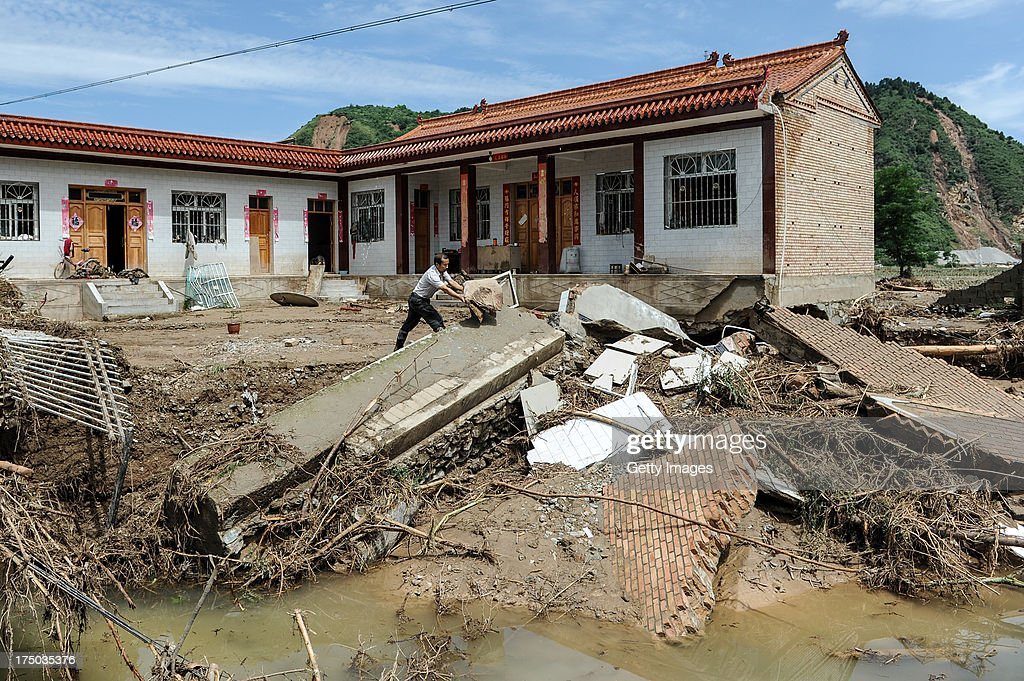 A villager cleans up the mud at his home on July 29, 2013 in Tianshui, China. At least 24 people were killed, with one person still missing, after rainstorm-triggered floods and landslides hit many areas of Tianshui city recently.