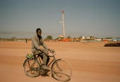 A villager cycles past an Exxon Mobil rig at Kome The pipeline will carry oil from the landlocked oil fields of Chad through the jungles of Cameroon...