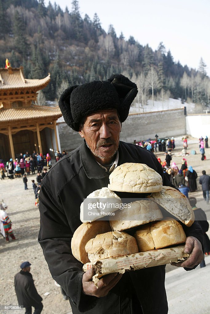 A villager donates his bread to lamas as offerings during the 'Tiaoqian' praying ceremony at the Youning Temple on February 8, 2009 in Huzhu County of Qinghai Province, China. The Youning Temple holds the annual 'Tiaoqian' ceremony in the first lunar month each year. During the ceremony, monks will wear colourful traditional clothes and masks, performing the 'Fawang Dance' and 'Horse-headed Warrior Dance' to scare away evil spirits. Pilgrims also pray for good luck during the ceremony.