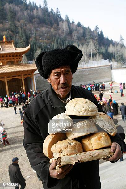 A villager donates his bread to lamas as offerings during the 'Tiaoqian' praying ceremony at the Youning Temple on February 8 2009 in Huzhu County of...