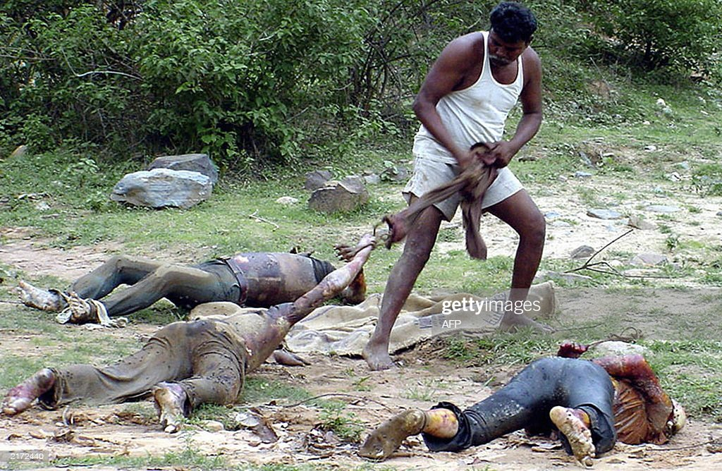 A villager drags the body of one three unidentified men alledgedly killed by outlawed Maoist Communist Centre extremists outside Rada village 30 June...