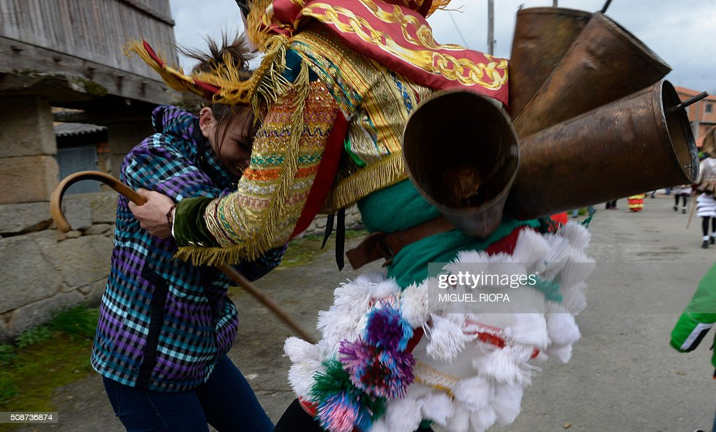 A villager dressed as a 'Felo' jokes with a woman during the traditional and ancestral carnival close to the village of Maceda northwestern Spain on February 6, 2016. The 'Felos ' represent anarchic and rebellious spirits meant to instill fear into anyone who approaches them and are the 'authority' during the week of Carnival, meaning they can break the rules.The mask represents virility. AFP PHOTO/ MIGUEL RIOPA / AFP / MIGUEL RIOPA