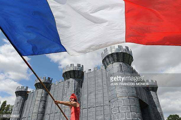 A villager dressed as Marianne personification of the French Revolution stands by a wooden and cardboard fortress and takes part in the commemorating...
