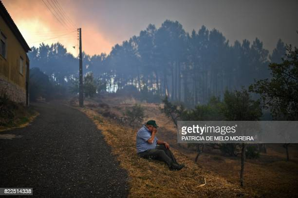 TOPSHOT A villager from Sanguinheira sits on the roadside as a wildfire approaches the village in Macao central Portugal on July 25 2017 / AFP PHOTO...