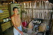 A villager grilling fish in the kitchen of his traditional reed hut in the village of Jaguarari The Floresta Nacional do Tapajos a 6500 km2 protected...