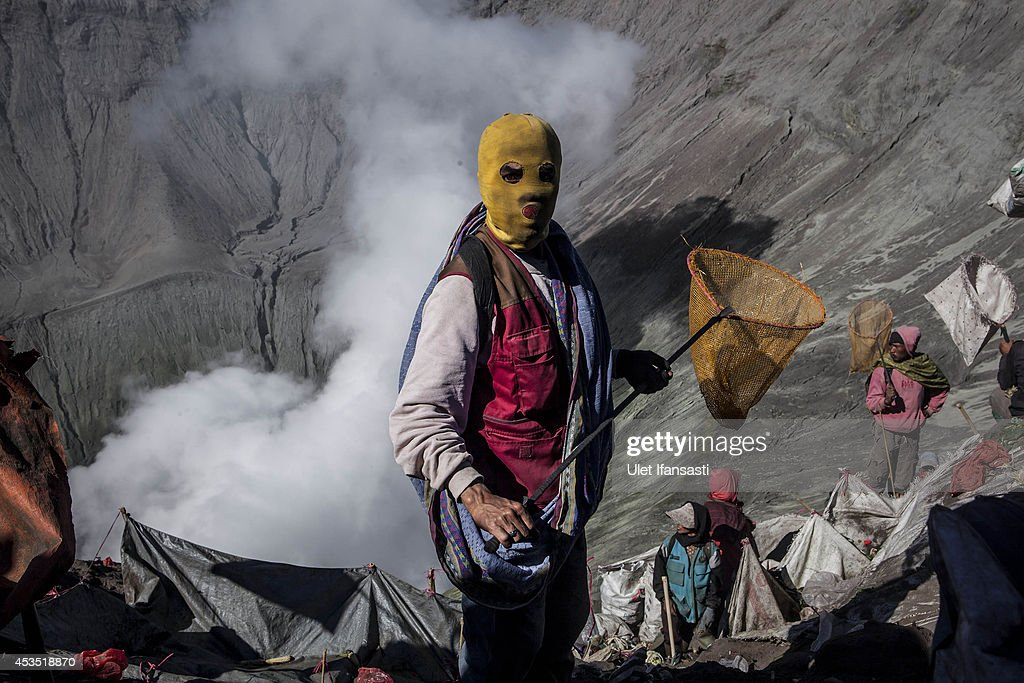 A villager holds a net as they wait to catch offerings thrown by Hindu worshippers during the Yadnya Kasada Festival at crater of Mount Bromo on August 12, 2014 in Probolinggo, East Java, Indonesia. The festival is the main festival of the Tenggerese people and lasts about a month. On the fourteenth day, the Tenggerese make the journey to Mount Bromo to make offerings of rice, fruits, vegetables, flowers and livestock to the mountain gods by throwing them into the volcano's caldera. The origin of the festival lies in the 15th century when a princess named Roro Anteng started the principality of Tengger with her husband Joko Seger, and the childless couple asked the mountain Gods for help in bearing children. The legend says the Gods granted them 24 children but on the provision that the 25th must be tossed into the volcano in sacrifice. The 25th child, Kesuma, was finally sacrificed in this way after initial refusal, and the tradition of throwing sacrifices into the caldera to appease the mountain Gods continues today.