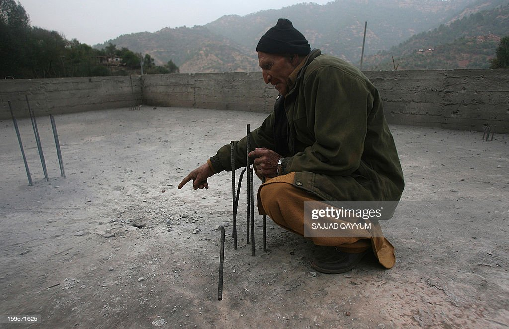 A villager in Pakistan-administered Kashmir, Muhammad Afsar points to the spot which was struck by mortar shrapnel at the village of Darra Sher Khan in Tatta Pani sector on January 16, 2013. India's army has reached an 'understanding' with Pakistan to 'de-escalate' military tensions in Kashmir after a recent deadly flare-up in the disputed border region, a spokesman told AFP. AFP PHOTO/Sajjad QAYYUM