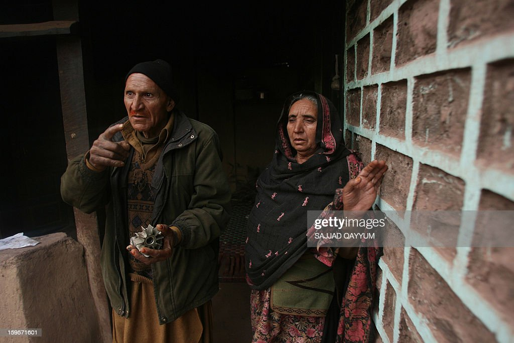 A villager in Pakistani-administered Kashmir, Muhammad Afsar (L), accompanied by his wife Zeenat Bibi, holds mortar shrapnel which hit his home at the village of Darra Sher Khan in Tatta Pani sector on January 16, 2013. India's army has reached an 'understanding' with Pakistan to 'de-escalate' military tensions in Kashmir after a recent deadly flare-up in the disputed border region, a spokesman told AFP. AFP PHOTO/Sajjad QAYYUM
