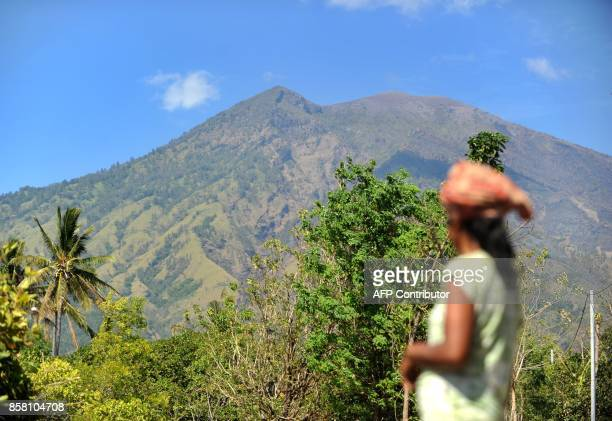 A villager looks at Mount Agung volcano from the Kubu subdistrict in Karangasem Regency on Indonesia's resort island of Bali on October 6 2017...