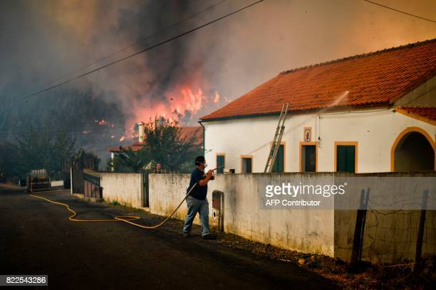 TOPSHOT A villager of Sanguinheira wets the roof of his house with a hose as a wildfire approaches in Macao central Portugal on July 25 2017 / AFP...