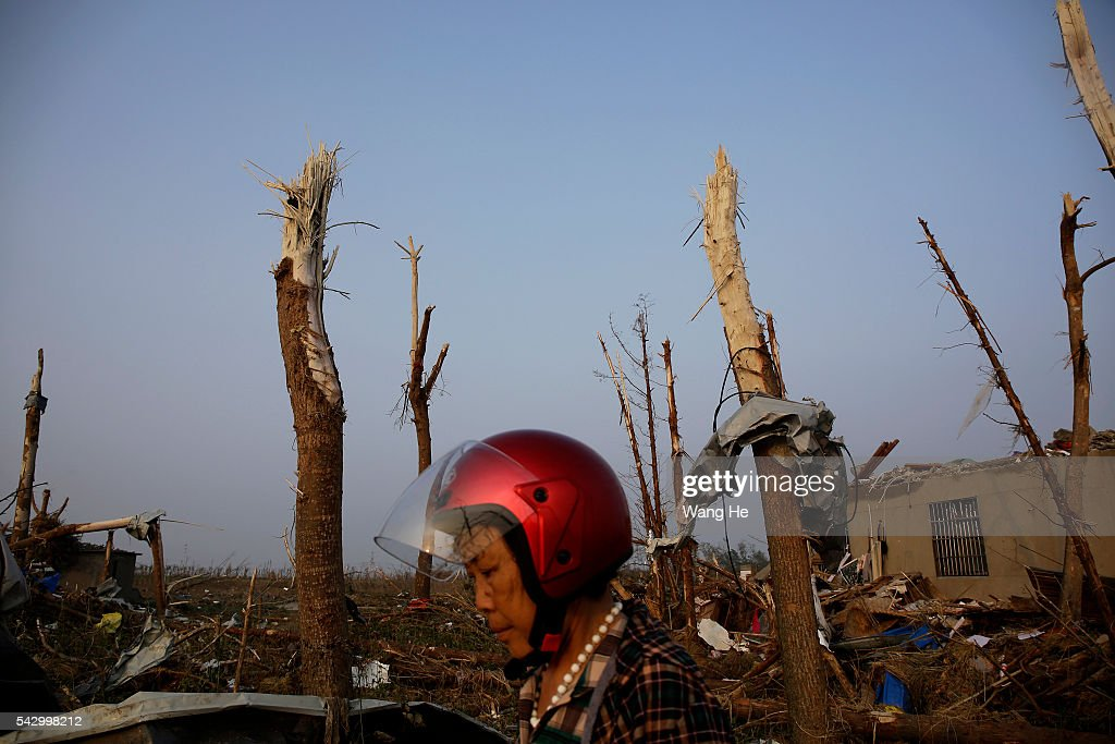 A villager passes through debris in Beichen Village of Chenliang Township in Funing, Yancheng, east China's Jiangsu Province on June 25, 2016. A total of 98 people were killed after severe storms in several towns in Jiangsu on Thursday, local rescue headquarters said on Friday. About 846 people sustained injuries, 200 of whom were seriously wounded, it said. More than 8,600 houses, two elementary schools and eight factory buildings were damaged in the counties of Funing and Sheyang, and parts of Yancheng City along the eastern coast of China on June 25, 2016 in Yancheng, China.