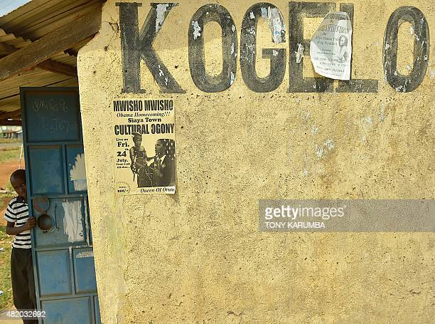 A villager peeks from behind a door next to a flyer advertising a concert to celebrate visiting US President Barack Obama's 'homecoming' to the east...