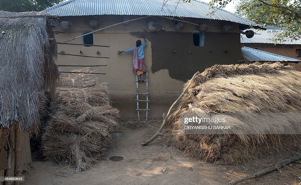 A villager plasters cow dung on the wall of her house following an alleged gang-rape in Subalpur village in Birdhum district, some 240 kilometres (149 miles) north west of Kolkata, on January 24, 2014. Male residents fled an Indian village January 24 after the alleged gang-rape of a young woman on the orders of tribal elders as police told of how locals tried to prevent her from reporting her ordeal. A total of 13 men have been arrested over the assault on a 20-year-old in the village of Subalpur, which was allegedly as punishment for 'dishonouring' her community. AFP PHOTO/Dibyangshu SARKAR