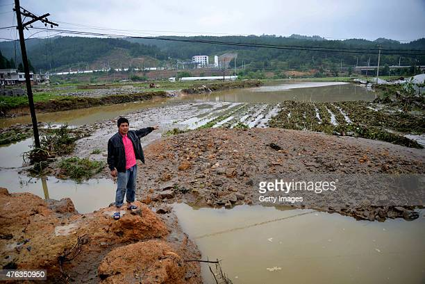 A villager points at a field which was damaged by flooding at Longshan County on June 8 2015 in Buyi and Miao Autonomous Prefecture of Qiannan...