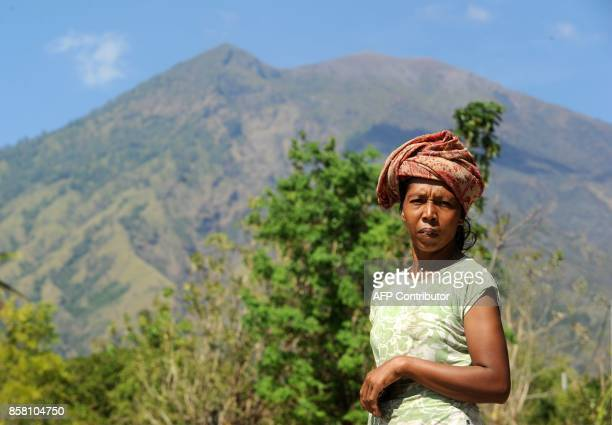 A villager poses as Mount Agung volcano looms in the background in the Kubu subdistrict in Karangasem Regency on Indonesia's resort island of Bali on...