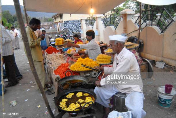 A villager prepares Jalebis, a sweet dish and other local sweets for sale during a local fair at Dimba village, district Pune