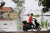 A villager riding Bicycle near the flood in Niushan Lake on July 14 2016 in Wuhan Hubei Province China Armed police destroyed the 37kilometerlong...