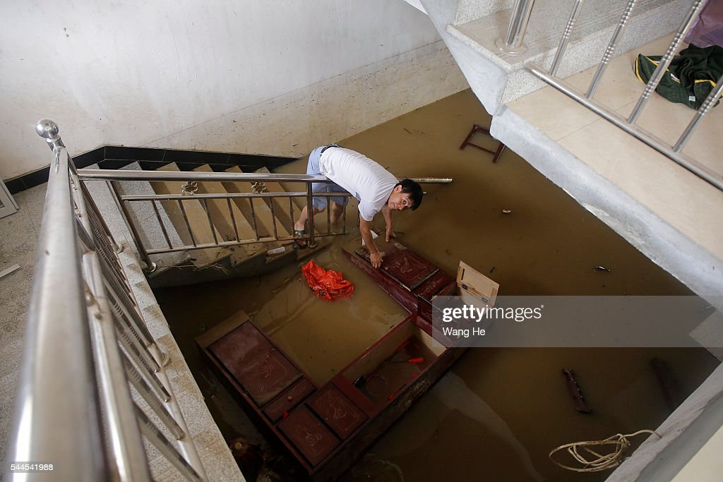 Villager searches for flooded articles at him house after Jushui River broke the dyke and flooded XuJiaDun village in Wuhan in central China's Hubei...