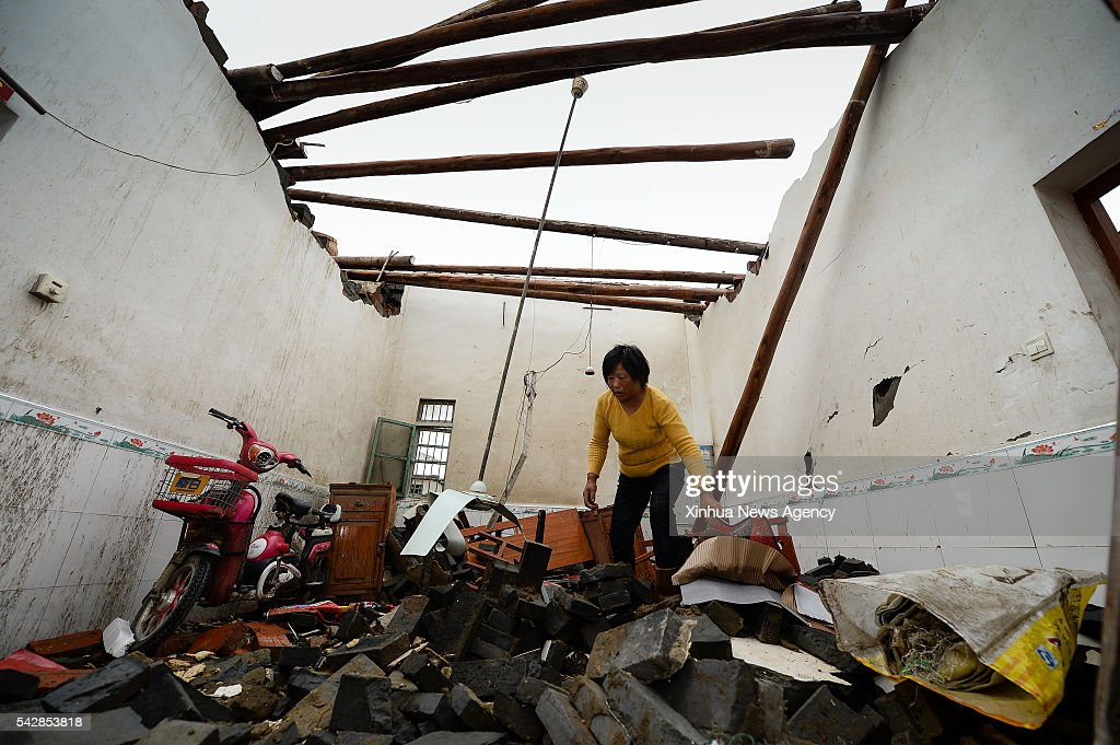 Villager Sun Sumei searches for undamaged articles at her house in Danping Village of Chenliang Township in Funing, Yancheng, east China's Jiangsu Province, June 24, 2016. A total of 98 people were killed after severe storms in several towns in Jiangsu on Thursday, local rescue headquarters said on Friday. About 846 people sustained injuries, 200 of whom were seriously wounded, it said. More than 8,600 houses, two elementary schools and eight factory buildings were damaged in the counties of Funing and Sheyang, and parts of Yancheng City along the eastern coast of China.